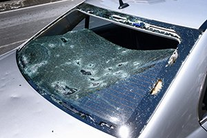 A photo of a car damaged by hail. Showing a broken rear window.